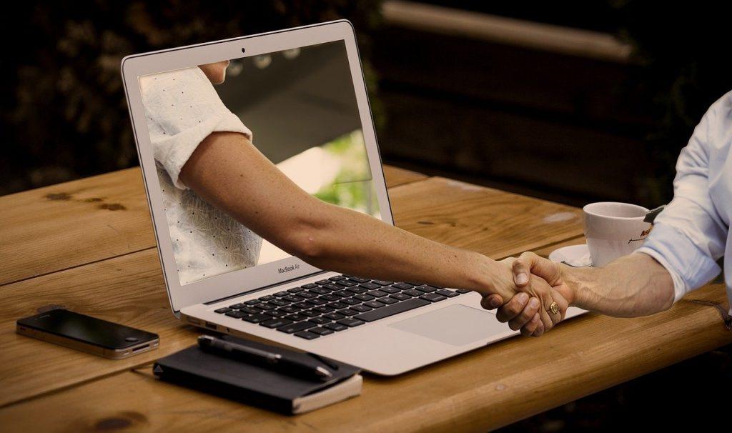 image représentant deux personne qui se tiennent la main à travers un ordinateur - Vaniseo, votre agence webmarketing et Googleads et référencement naturel marseille