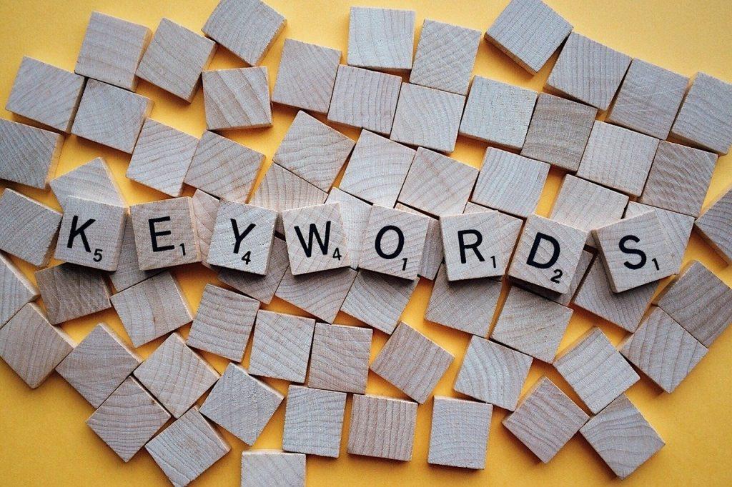 Lettres de mots-clés en bois sur fond jaune - Vaniseo - votre agence adwords marseille